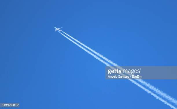 low angle view of airplane flying against clear blue sky - vliegtuigdamp stockfoto's en -beelden