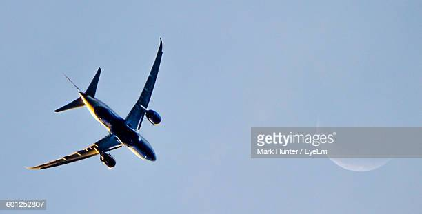 Low Angle View Of Airplane Flying Against Clear Sky