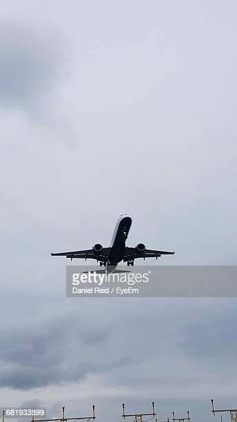 low angle view of airplane flying against cloudy sky - reid,_wisconsin stock pictures, royalty-free photos & images