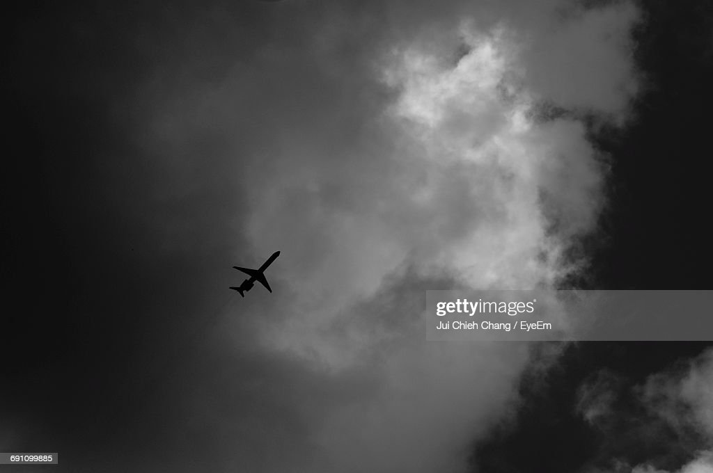 Low Angle View Of Airplane Flying Against Cloudy Sky : Stock Photo