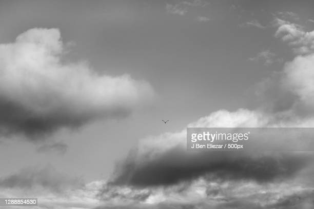 low angle view of airplane flying against cloudy sky,agoura hills,california,united states,usa - agoura hills stock pictures, royalty-free photos & images