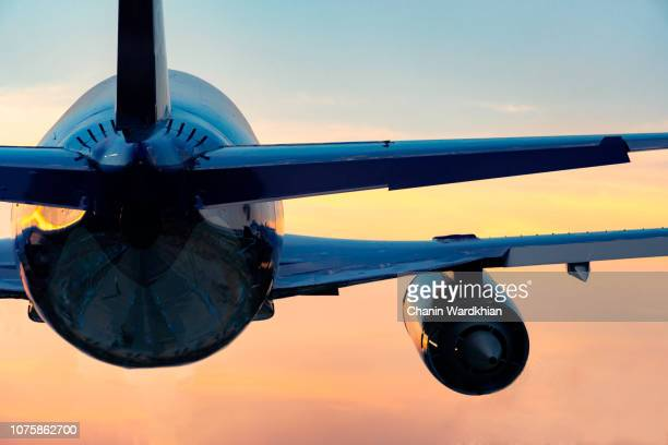 low angle view of airplane flying against sky during sunset - aeroplane stock photos and pictures