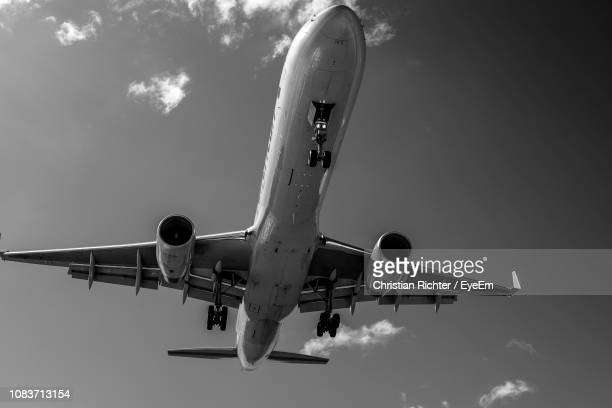 "low angle view of airplane flying against sky - ""christian richter"" stock pictures, royalty-free photos & images"