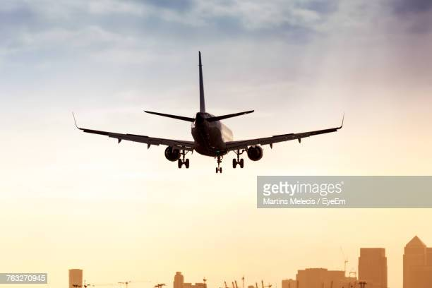 low angle view of airplane flying against sky - airplane stock photos and pictures