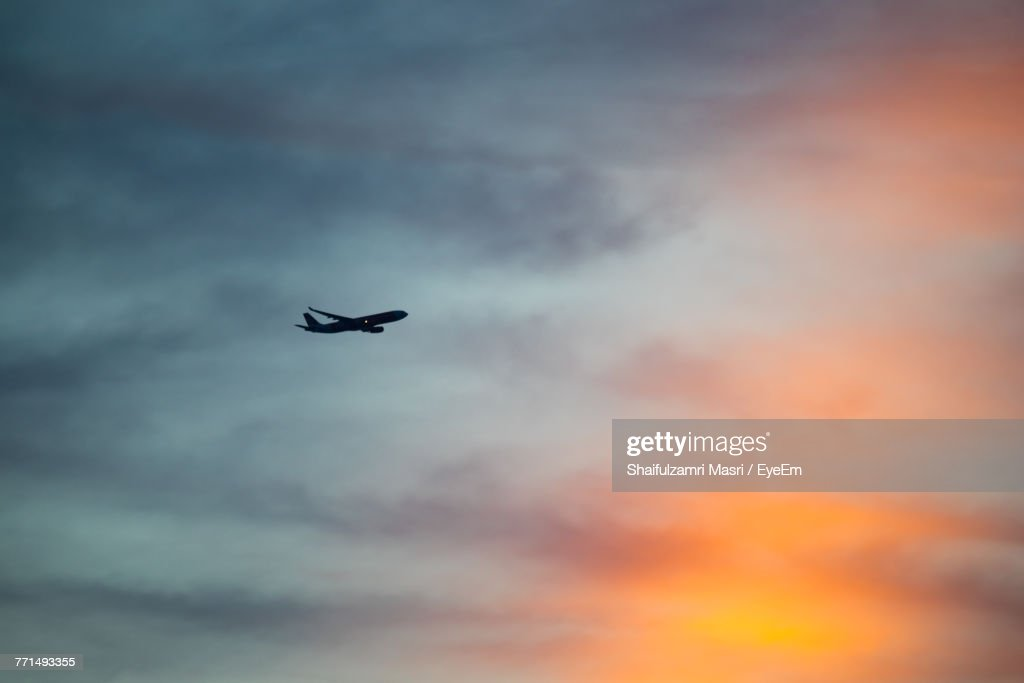 Low Angle View Of Airplane Flying Against Sky : Stock Photo