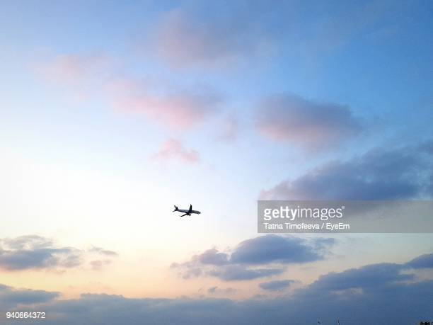 low angle view of airplane flying against sky - airplane sky stock pictures, royalty-free photos & images