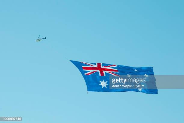low angle view of airplane flying australian flag against clear blue sky - helicopter stock pictures, royalty-free photos & images