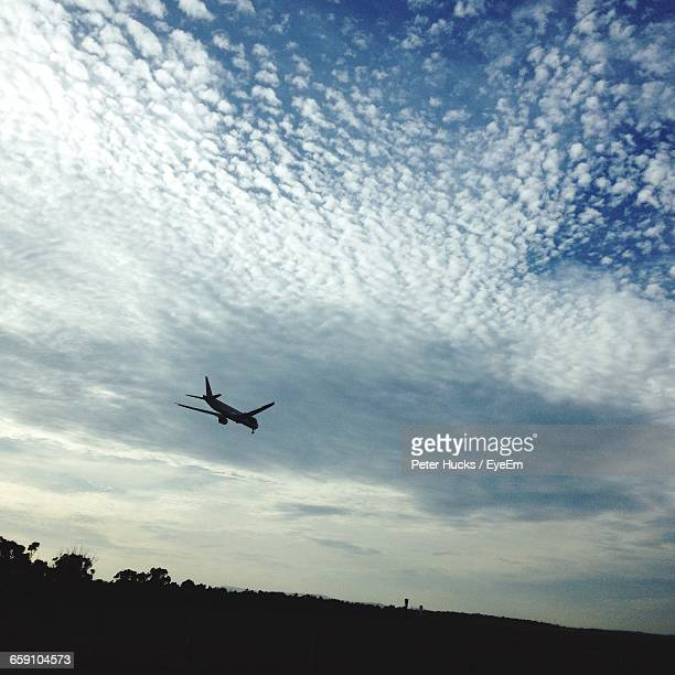 low angle view of airplane flying in cloudy sky - st. albans stock pictures, royalty-free photos & images