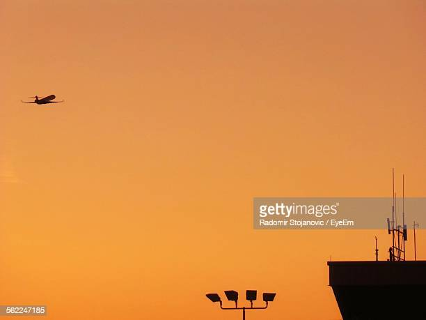 Low Angle View Of Airplane Flying In Orange Sky