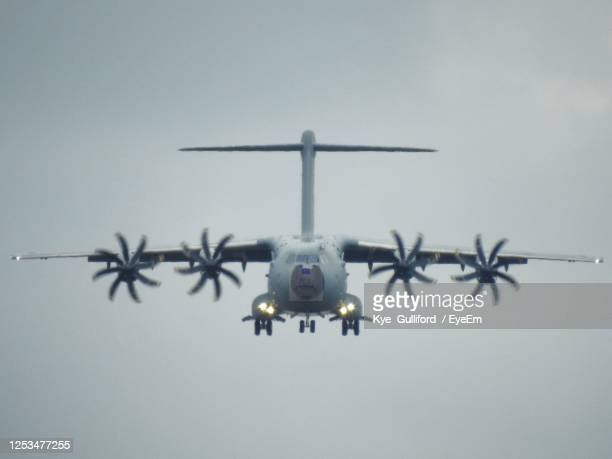 low angle view of airplane flying in sky over sea - british military stock pictures, royalty-free photos & images