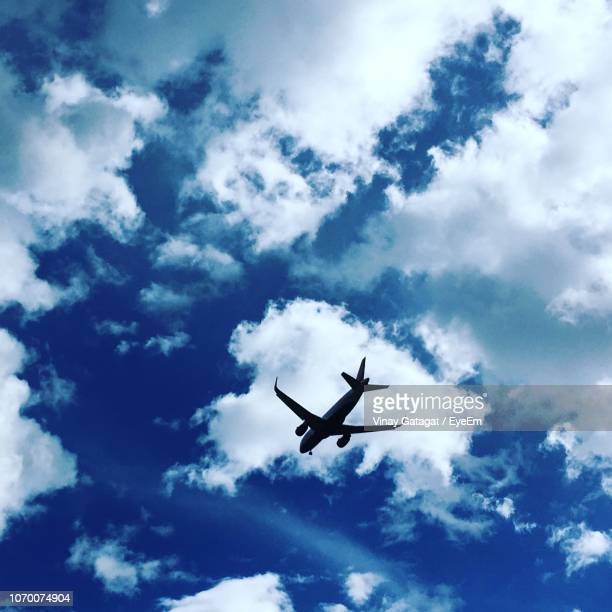 low angle view of airplane flying in sky - paro district stock pictures, royalty-free photos & images