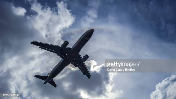 low angle view of airplane flying in sky - airport stock pictures, royalty-free photos & images