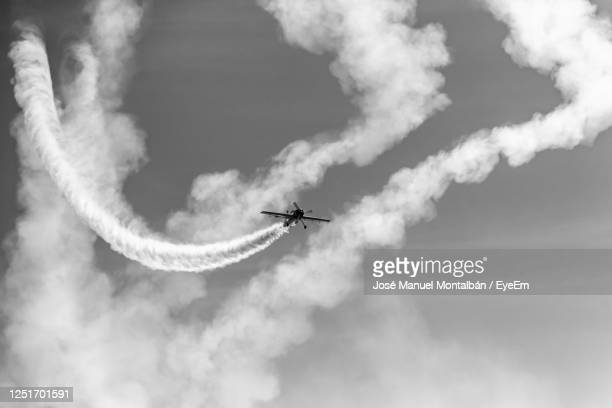 low angle view of airplane flying in sky - 航空ショー ストックフォトと画像