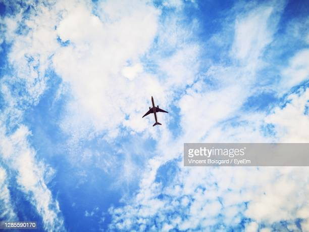 low angle view of airplane flying in sky - aeroplane stock pictures, royalty-free photos & images