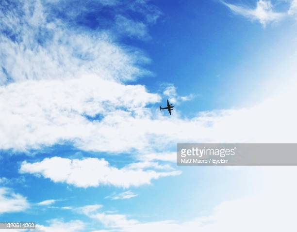 low angle view of airplane flying in sky - truro cornwall stock pictures, royalty-free photos & images