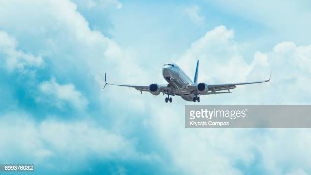 low angle view of airplane flying in sky - plane stock photos and pictures
