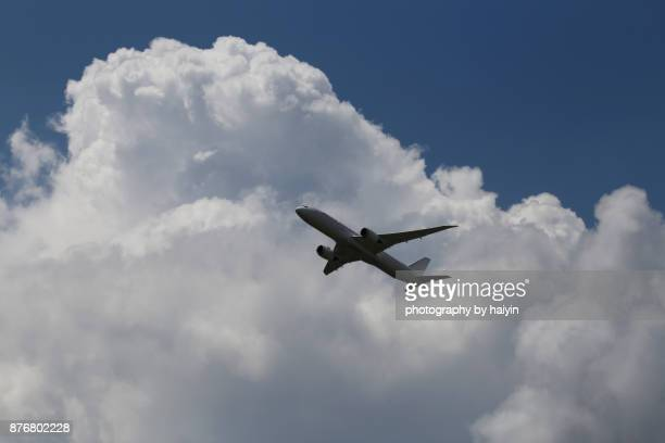 Low Angle View Of Airplane Flying In The Dramatic Cloud