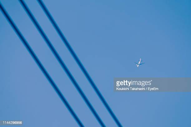 Low Angle View Of Airplane Flying Over Cables Against Clear Blue Sky