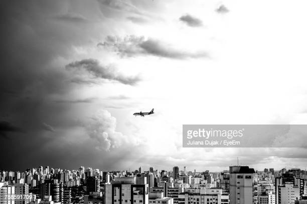 Low Angle View Of Airplane Flying Over City Against Sky