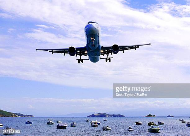 Low Angle View Of Airplane Flying Over Sea Against Sky