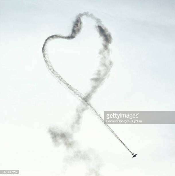 Low Angle View Of Airplane Vapor Trail Making Heart Shape In Sky