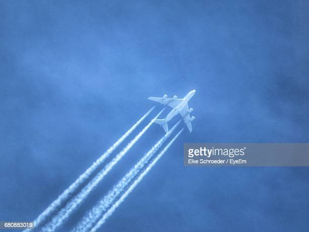 Low Angle View Of Airplane With Trails In Flight
