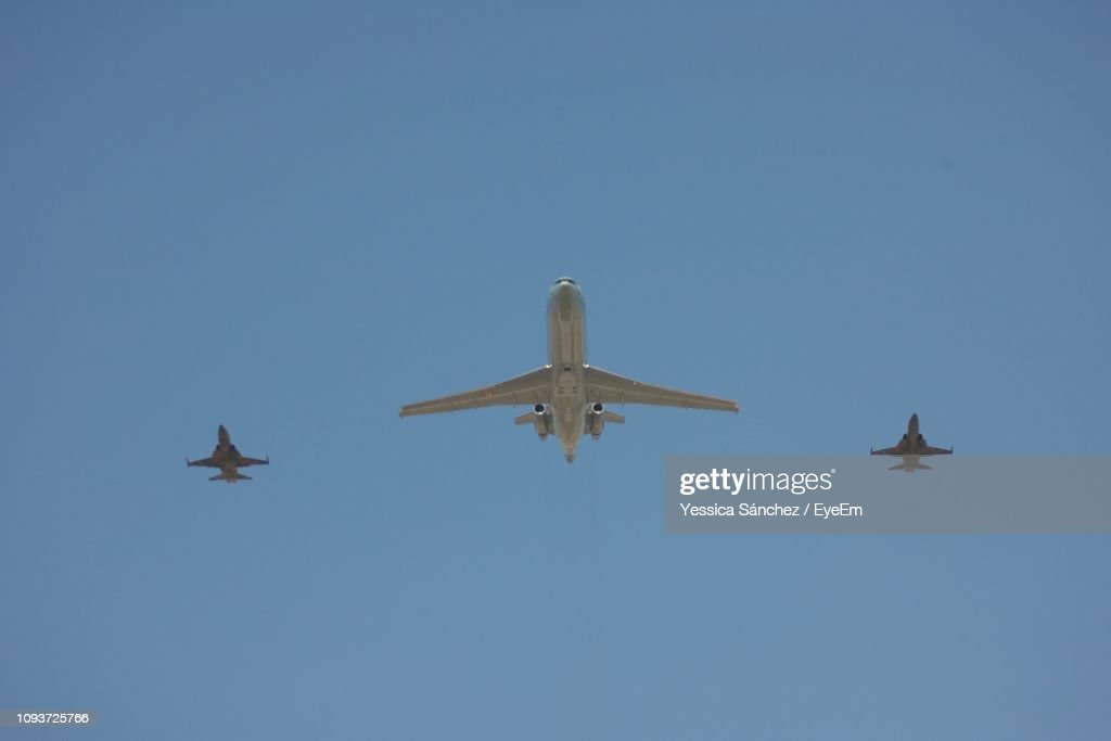 Low Angle View Of Airplanes Flying Against Clear Blue Sky : Foto de stock