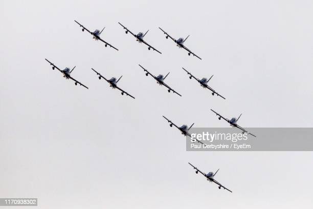 low angle view of airplanes flying against clear sky - military airplane stock pictures, royalty-free photos & images