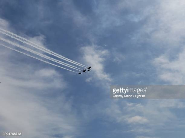 low angle view of airplanes flying against sky - military parade stock pictures, royalty-free photos & images