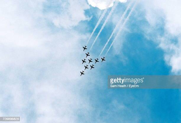 low angle view of airplanes flying in sky - military airplane stock pictures, royalty-free photos & images