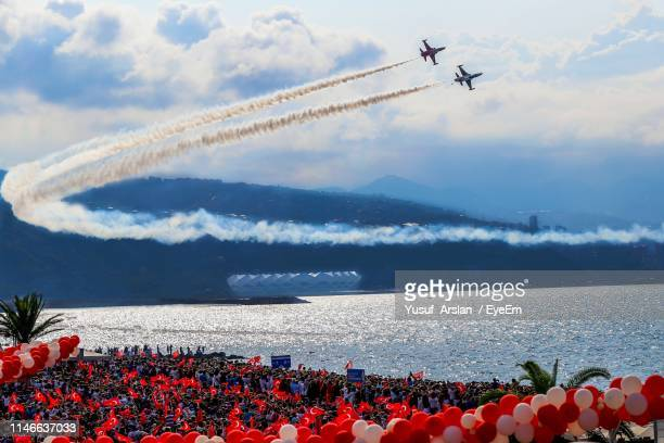 low angle view of airplanes flying over lake against cloudy sky - 航空ショー ストックフォトと画像