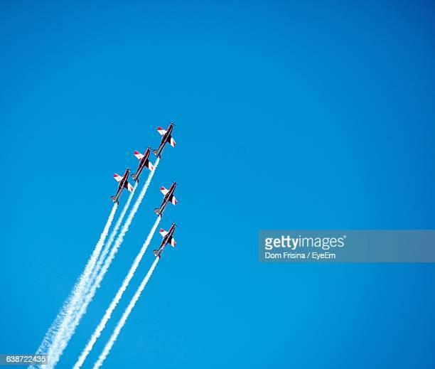 Low Angle View Of Airplanes Performing Air Show In Clear Blue Sky