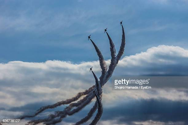 Low Angle View Of Airplanes Performing Airshow In Cloudy Sky
