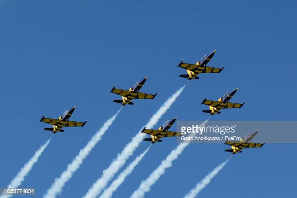 low angle view of airshow against clear blue sky - low flying aircraft stock pictures, royalty-free photos & images