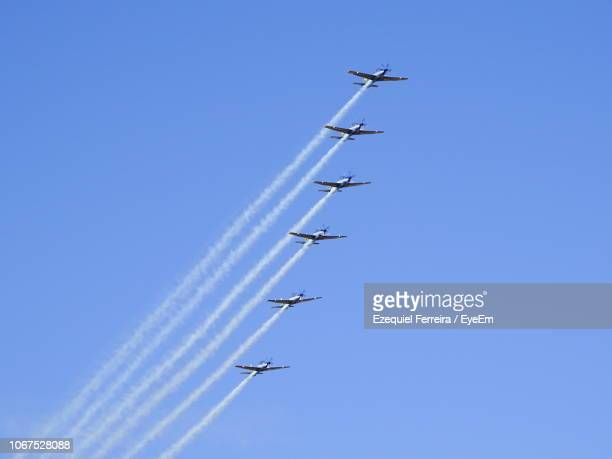 low angle view of airshow against clear blue sky - 航空ショー ストックフォトと画像