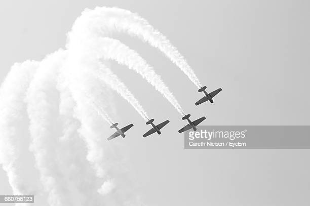 low angle view of airshow against cloudy sky - 航空ショー ストックフォトと画像