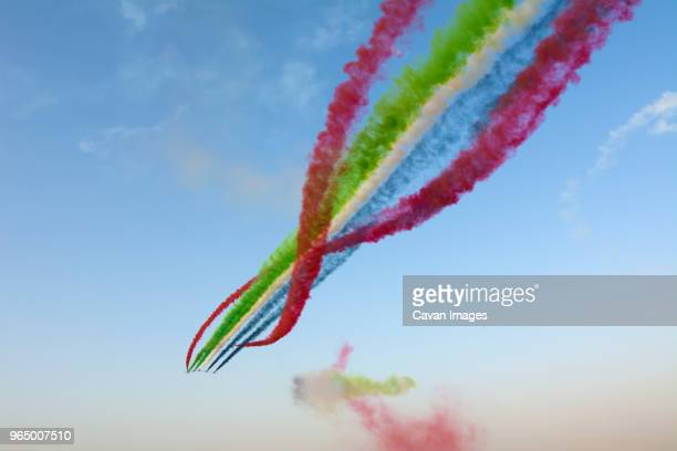 low angle view of airshow against sky - coordinazione foto e immagini stock