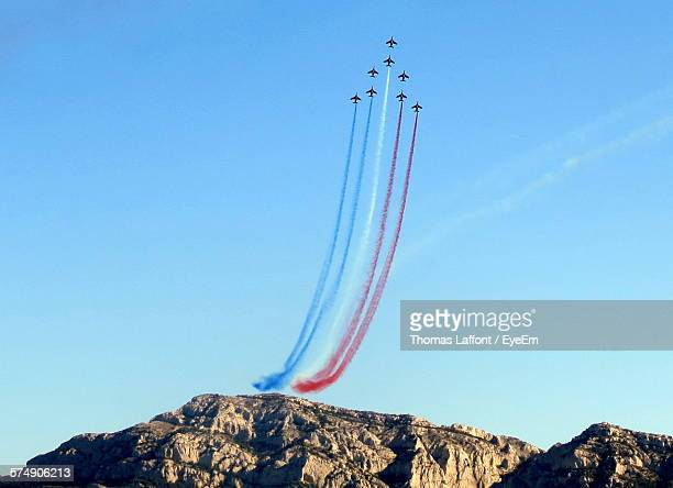 Low Angle View Of Airshow Over Mountain Against Blue Sky