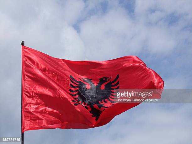 low angle view of albanian flag against sky - bandiera albanese foto e immagini stock