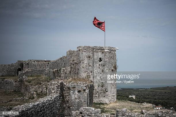 low angle view of albanian flag on old ruin against sky - bandiera albanese foto e immagini stock
