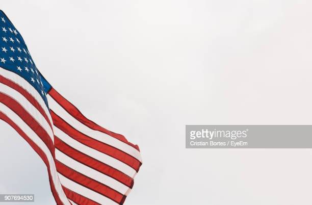 low angle view of american flag against clear sky - bortes stock-fotos und bilder