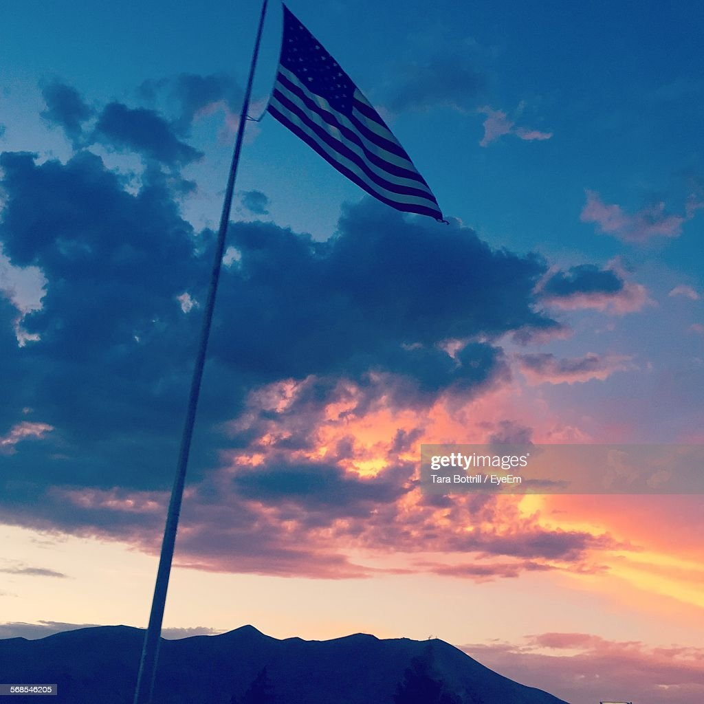 Low Angle View Of American Flag Against Cloudy Sky At Sunset : Stock Photo