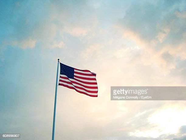 Low Angle View Of American Flag Against Cloudy Sky