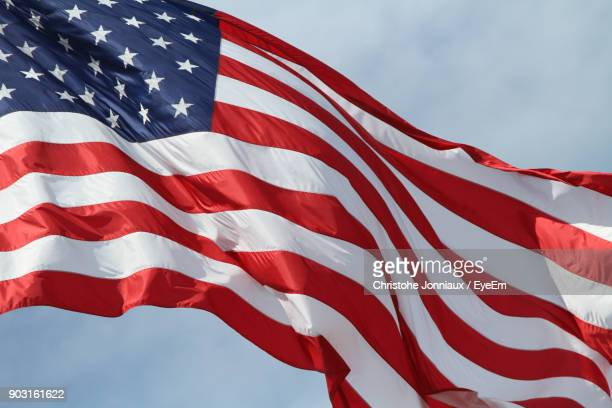 low angle view of american flag against sky - stars and stripes stock pictures, royalty-free photos & images
