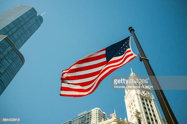 Low Angle View Of American Flag And City Buildings Against Clear Blue Sky