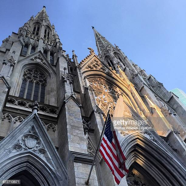 Low Angle View Of American Flag At St Patrick Cathedral Against Clear Sky In City