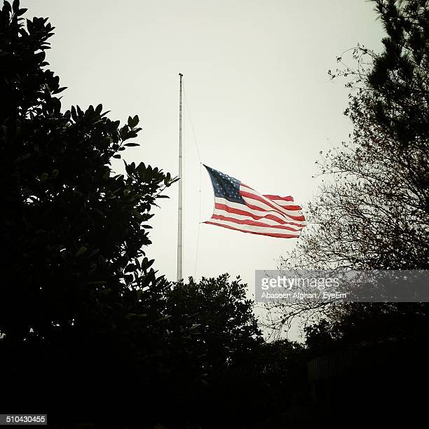 low angle view of american flag fluttering against clear sky - half mast stock photos and pictures