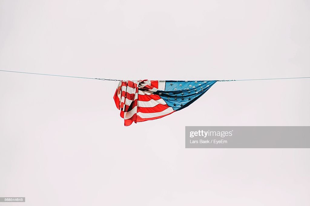 Low Angle View Of American Flag Hanging From Rope Against Clear Sky : Stock Photo