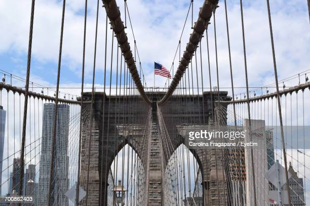 low angle view of american flag on brooklyn bridge against sky - carolina fragapane stock pictures, royalty-free photos & images