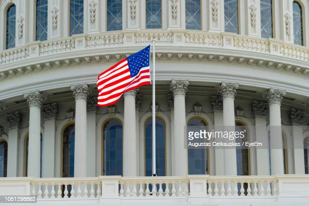 low angle view of american flag on railing by building in city - capital cities stock photos and pictures